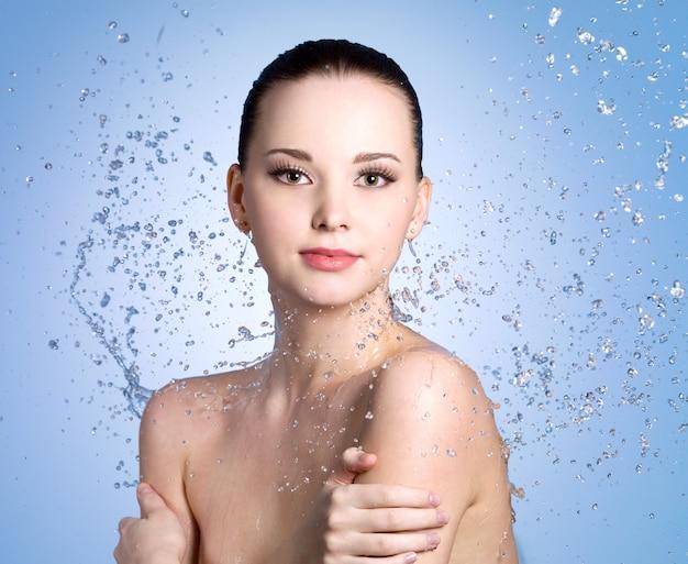 Salpicos de água na bela jovem com pele limpa - fundo colorido Foto gratuita