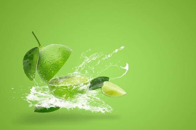 Salpicos de água no limão verde fresco isolado em fundo verde Foto Premium