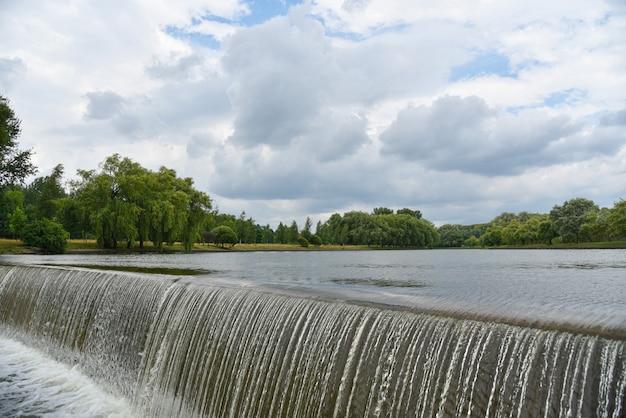 Salpicos de uma cachoeira em um rio em um parque da cidade Foto Premium