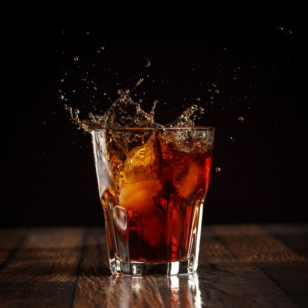 Salpicos no copo de coca-cola com gelo no fundo gradiente cinza Foto Premium