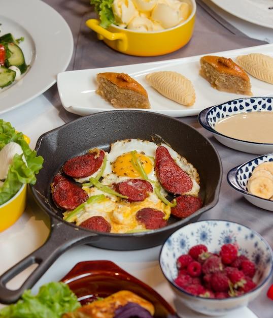 Salsicha e ovo no café da manhã com doces, frutas, bagas Foto gratuita