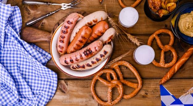 Salsichas alemãs tradicionais e brezel de pastelaria para um festival de cerveja. madeira e decoração. vista de cima Foto Premium