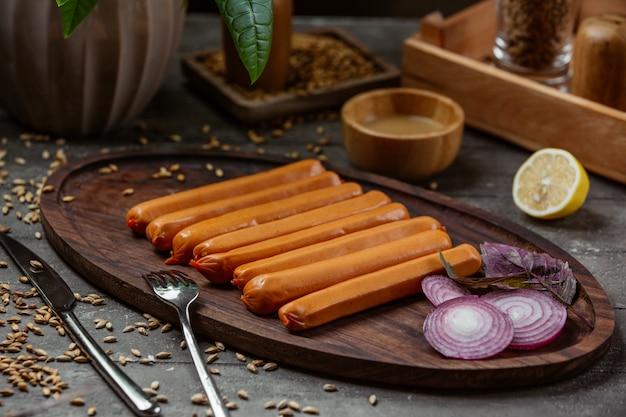 Salsichas cozidas na bandeja de madeira com fatias de cebola vermelha Foto gratuita