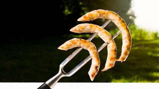 Salsichas de churrasco amarradas no garfo Foto gratuita