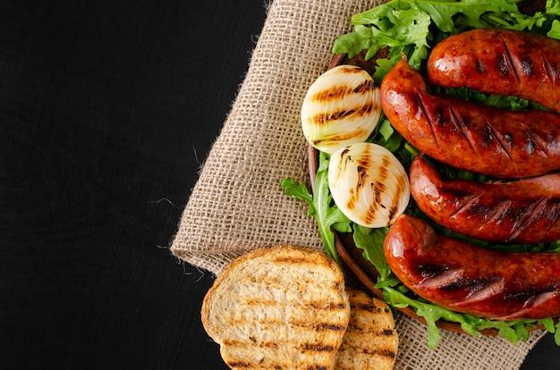 Salsichas de churrasco, torradas de pão, cebola e rúcula fresca em fundo preto. configuração plana Foto Premium