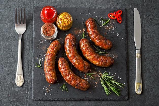 Salsichas de munique grelhado suculentas com especiarias em uma placa de pedra preta Foto Premium