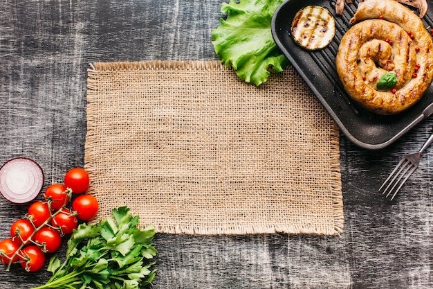 Salsichas espirais grelhadas na panela com vegetais orgânicos sobre fundo cinza de madeira Foto gratuita