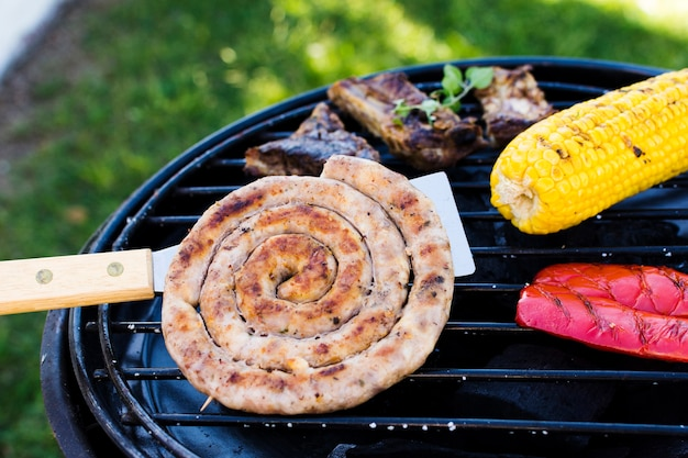 Salsichas espirais, legumes e carne na grelha Foto gratuita