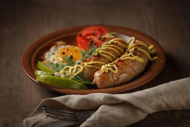 Salsichas fritas com especiarias, legumes e verduras. Foto Premium