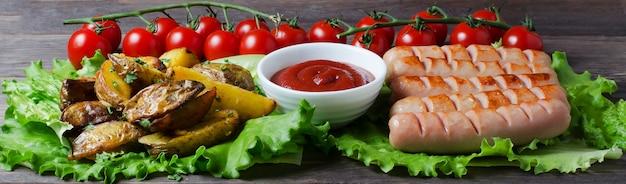Salsichas grelhadas em folhas de alface verde, molho de tomate, tomate cereja vermelho em um galho. madeira escura Foto Premium