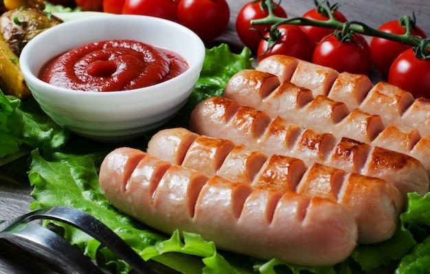 Salsichas grelhadas nas folhas verdes da alface, molho de tomate, tomate cereja vermelho em um galho. fundo escuro de madeira Foto Premium