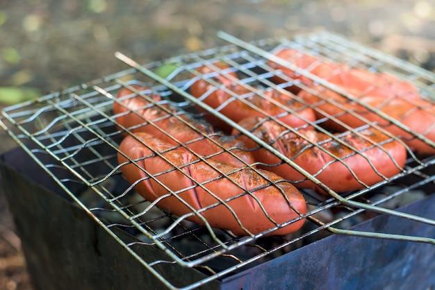 Salsichas na grelha sobre o fogo. Foto Premium