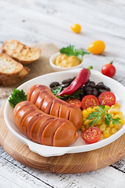 Salsichas na panela de grelhar na mesa de madeira Foto gratuita