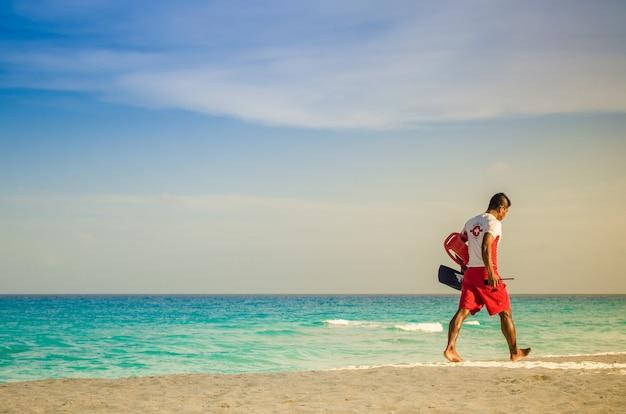 Salva-vidas caminhando na praia de cancún. Foto Premium