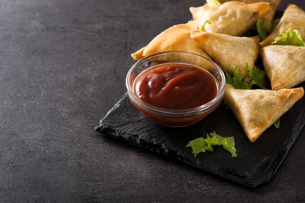 Samsa ou samosas com carne e legumes no preto. copyspace Foto Premium