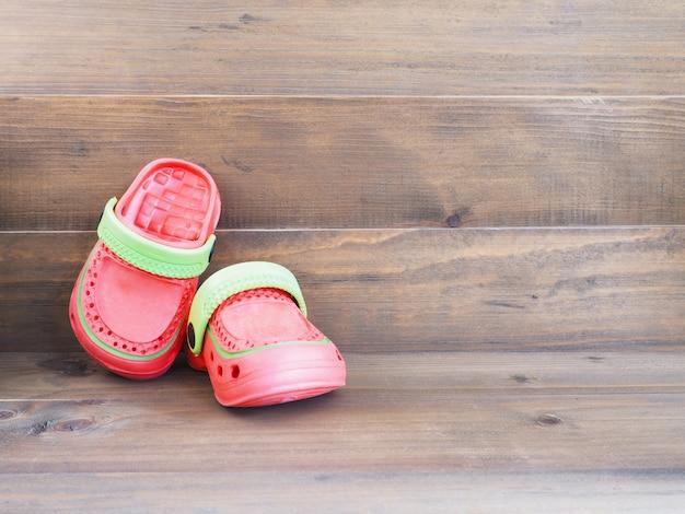 Sandálias de borracha infantil em fundo de madeira Foto Premium