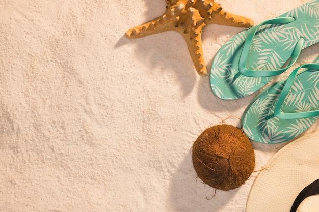 Sandálias de tanga de estrela do mar de coco e chapéu na areia Foto gratuita
