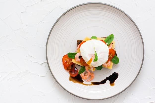 Sanduíche apetitoso com ovo escalfado, tomate, camarão e rúcula na placa. vista do topo Foto Premium