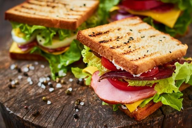 Sanduíche caseiro com presunto, alface, queijo e tomate em um fundo de madeira Foto Premium