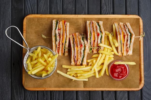 Sanduíche club com batatas fritas em cesta de metal Foto Premium