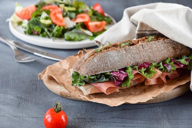 Sanduíche com baguete, presunto, alface, couve no fundo cinza Foto Premium