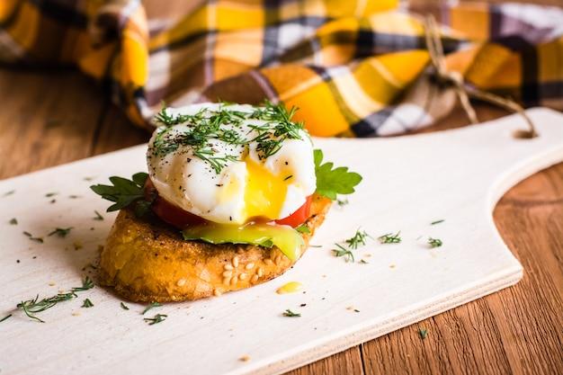 Sanduíche com ovo escalfado e tomate em uma placa de corte Foto Premium