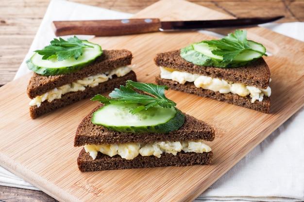 Sanduíche com ovos mexidos e pepinos em fundo rústico de madeira Foto Premium