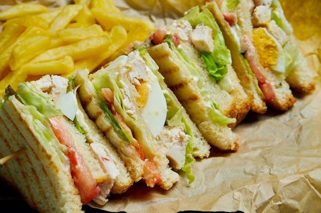 Sanduíche com presunto, tomate, pepino em conserva, ovo, queijo e alface em uma bandeja de madeira. fechar-se. saborosa comida rápida. Foto Premium