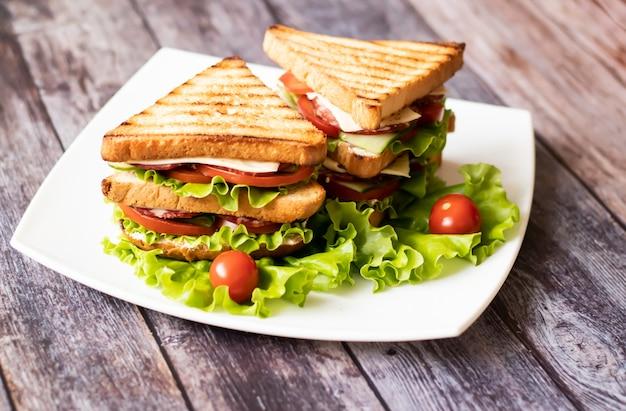 Sanduíche com queijo, tomate, pepino, salsicha e salada na madeira Foto Premium