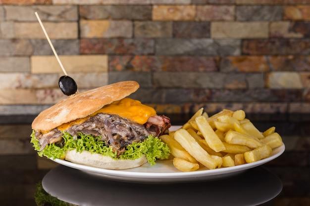 Sanduíche de carne com queijo cheddar, cogumelos, cebola, alface, tomate, bacon e batata frita Foto Premium