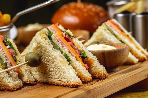Sanduíche de clube de vista lateral com presunto em conserva pepino alface tomate queijo e molho em uma placa Foto gratuita