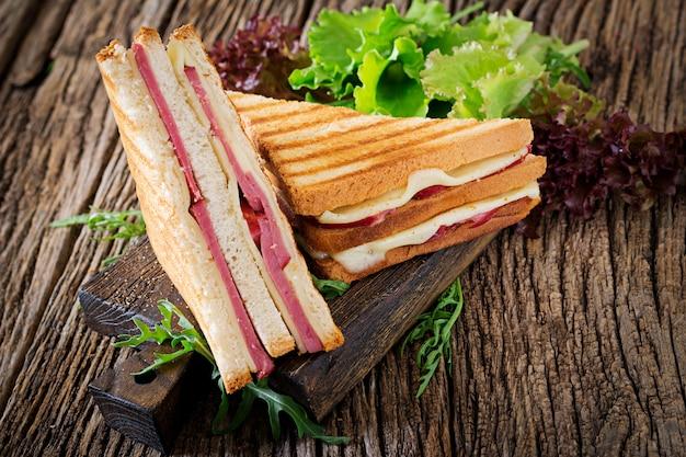 Sanduíche de clube - panini com presunto e queijo na mesa de madeira. comida para piquenique. Foto gratuita