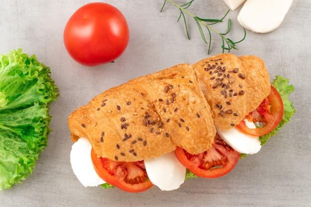 Sanduíche de croissant com mussarela e tomate alface. lanche saudável. Foto Premium