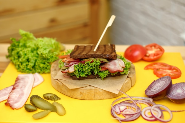 Sanduíche de pão escuro grelhado na placa de madeira na placa amarela Foto Premium