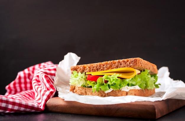 Sanduíche delicioso ao lado de uma toalha de mesa Foto gratuita