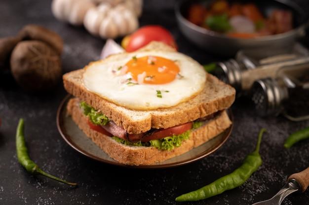 Sanduíche do café da manhã feito com pão, ovo estrelado, presunto e alface. Foto gratuita