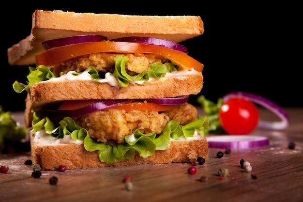 Sanduíche duplo, com frango, alface, tomate, cebola, pimenta e molho, sobre uma mesa de madeira e fundo preto. Foto Premium
