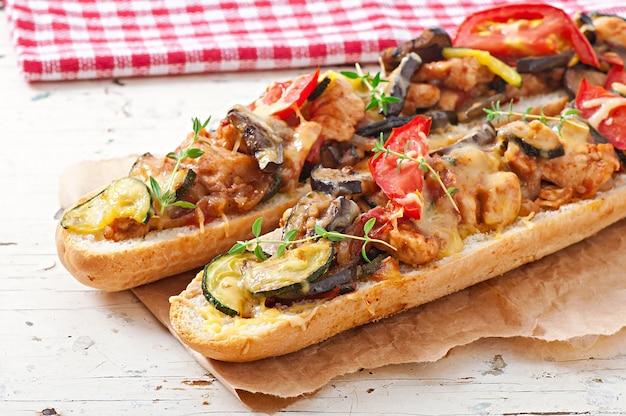 Sanduíche grande com legumes assados (abobrinha, berinjela, tomate) com queijo e tomilho Foto gratuita