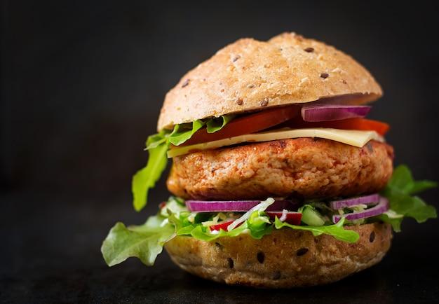 Sanduíche grande - hambúrguer com hambúrguer de frango suculento, queijo, tomate e cebola vermelha na mesa preta Foto gratuita