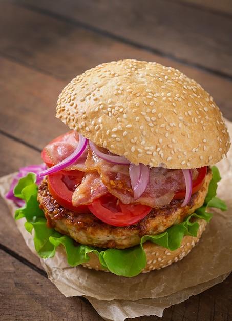 Sanduíche grande - hambúrguer hambúrguer com carne, cebola roxa, tomate e bacon frito. Foto gratuita