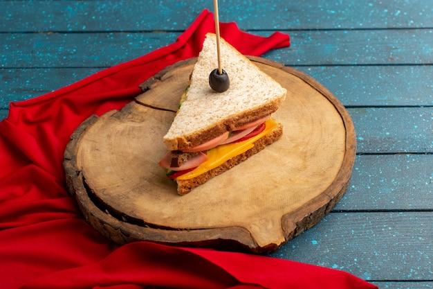 Sanduíche saboroso de vista frontal com presunto de queijo dentro da mesa de madeira azul Foto gratuita