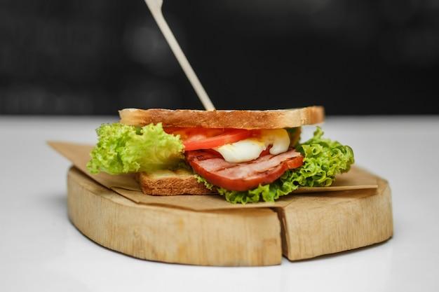 Sanduíche suculento com pão grelhado e bacon na placa de madeira Foto Premium