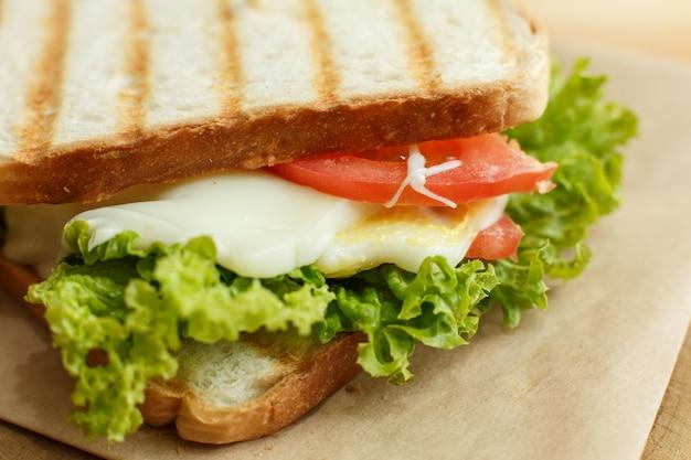 Sanduíche suculento do close up com bacon, os legumes frescos, a salada verde e linhas escuras após a grade. Foto Premium