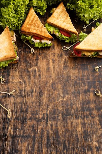 Sanduíche triangular alto com tomate e salada Foto gratuita
