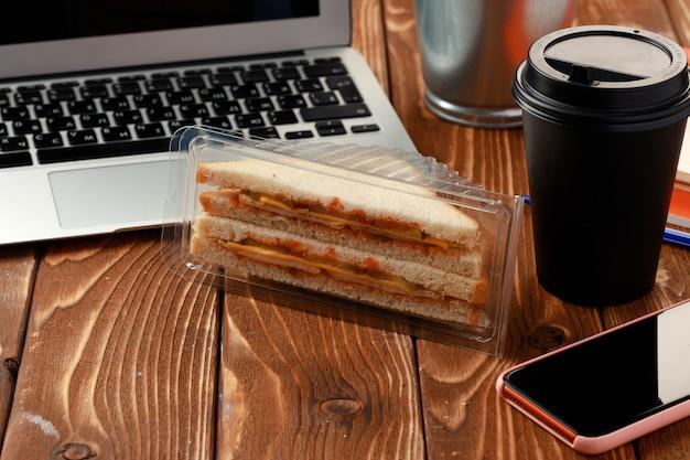 Sanduíche triangular na mesa de madeira do escritório com laptop e xícara de café Foto Premium