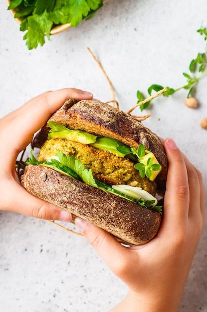 Sanduíche vegano com patty de grão de bico, abacate, pepino e verduras no pão de centeio Foto Premium