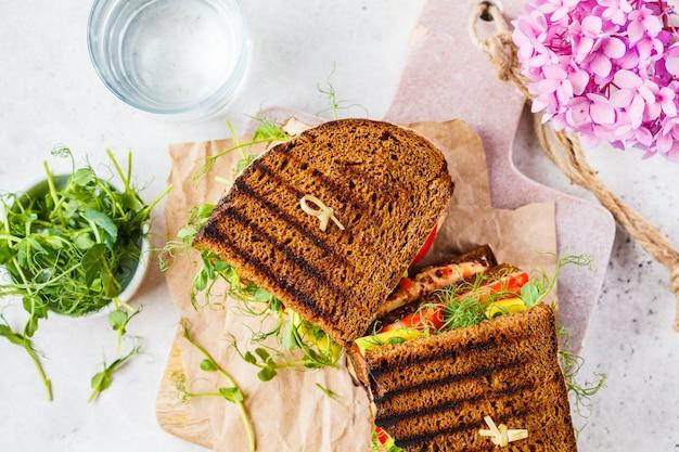 Sanduíche vegano com tofu, hummus, abacate, tomate e couve. Foto Premium