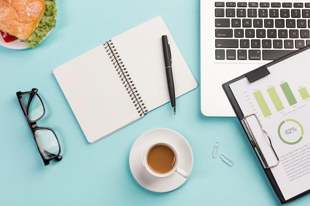 Sanduíche, xícara de café, óculos, bloco de notas em espiral, caneta, laptop e prancheta com o plano de orçamento na mesa azul Foto gratuita