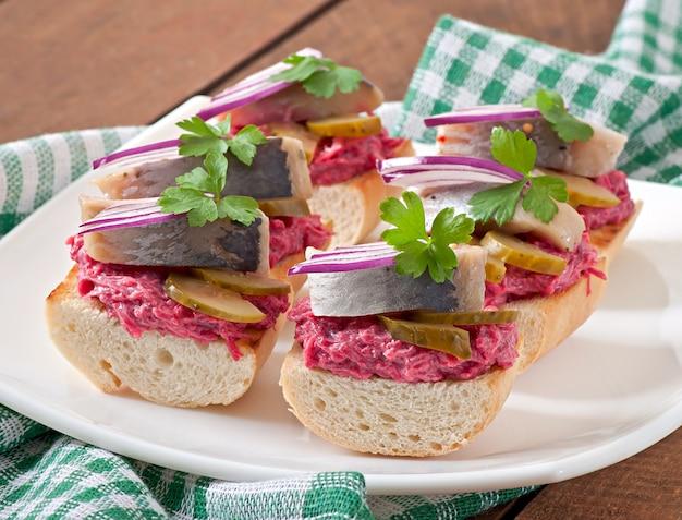 Sanduíches com arenque, beterraba e pepino em conserva Foto Premium