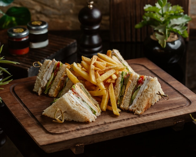 Sanduíches com batatas fritas em uma placa de madeira Foto gratuita